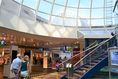 Glaskuppel des Allee-Centers mit unterschiedlichen Geschäften und einer Treppe, die zu den Stadtwerden/der ewr führt.
