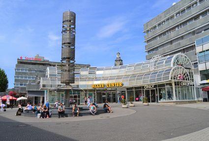 Haupteingang des Einkaufscenters Allee Centers mit einem Brunnen im Vordergrund, auf dessen Rand mehrere Menschen sitzen.